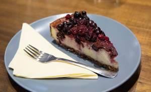 Stück hausgemachter Käsekuchen mit Beeren als Nachtisch auf blauem Teller