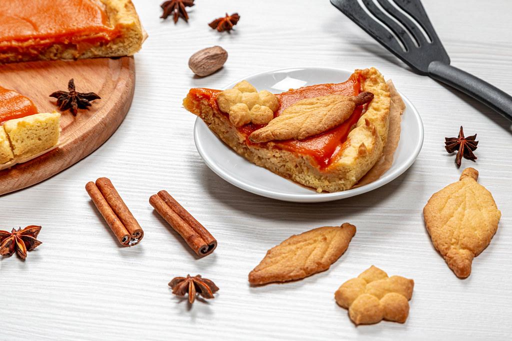 Stück von Kürbiskuchen mit Zimt, Anissternen und Keksen auf einem weißen Tisch