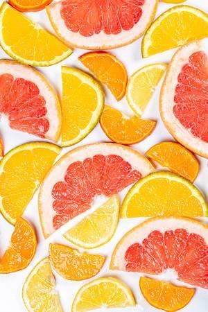 Stückchen von frischen Zitrusfrüchten vor weißem Hintergrund aus oben fotografiert