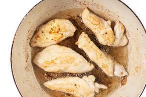 Stücke Hähnchenfleisch werden mit Öl in Topf knusprig gebraten vor weißem Hintergrund