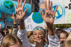 "Student wrote ""Act Now"" on both hands to protest climate politics during climate strike"