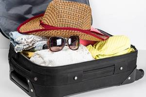 Suitcase preparation for a summer holiday with summer clothes, sunglasses and a hat