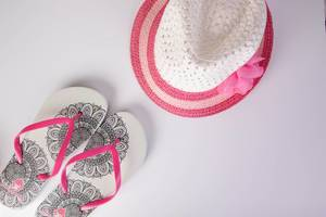 Summer flip flops and hat on white background
