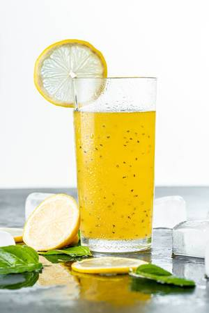 Summer yellow drink with lemon, mint leaves and ice