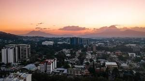 Sunset over Guatemala City Buildings over the Volcanoes on the Horizon.jpg