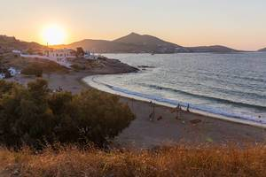 Sunset over Paros bathes beach and typical Greek buildings in golden light