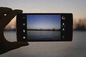 Sunset view through a smartphone taking a picture of it hold by a hand