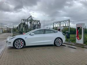 Supercharger charging station for electric cars: Tesla Model 3 with Long-Range-Batterie charges at the electric filling station in Erftstadt, Germany