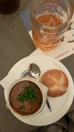 Suppe mit Brötchen und einem Maß Bier auf der Wiesn