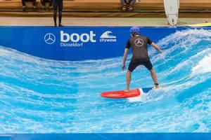 Surfer mit Surfbrett reitet stehende Welle the wave an Boot Düsseldorf