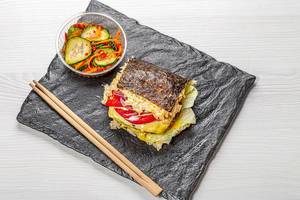 Sushi Burger on black background with spicy vegetables. Top view (Flip 2019)
