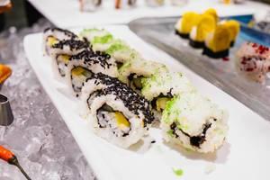 Sushi mit Sesamtopping auf einem langen Tablett am gekühlten Büfettstand