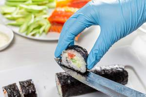 Sushi roll making preparation, close up on chef hands with a knife (Flip 2019)