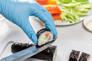 Sushi roll making preparation, close up on chef hands with a knife