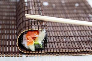 Sushi roll wrapped in bamboo Mat with chopsticks