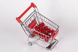 Süsse, knackig rote Kirschen in Einkaufswagen vor weißem Hintergrund