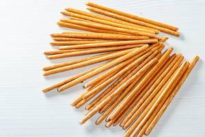Süße Cracker-Stäbchen ähnlich zu den zum Aperitif gereichten Grissinis auf weißem Tisch