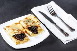 Süße Pfannkuchen mit Marmelade neben Besteck auf schwarzem Untergrund