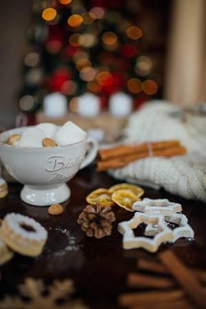 Süße Weihnachtsdekoration mit Keksen, Zimtstangen, getrockneten Orangenscheiben und Tannenzapfen