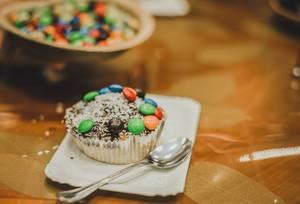 Süßer Muffin mit Schokoladeglasur, M&Ms und Kokosnussstreuseln auf Pappteller, im Hintergrund Schale mit M&Ms