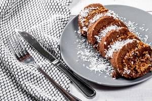 Süßer Nachtisch aus Schokoladen-Biskuit-Kuchen mit Kondensmilch, Kirschen und Kokosnussraspeln, auf einem gedeckten Tisch