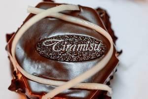 Süßer Tiramisu-Kuchen mit Schokoladenglasur und weißem Tiramisu-Schriftzug