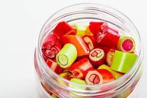 Süßigkeiten mit Früchte-Muster in einem Plastik Gefäß auf weißem Hintergrund