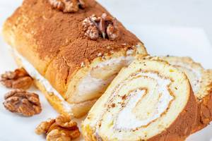 Sweet biscuit roll with cream and walnuts
