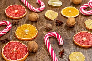 Sweet Christmas cane-lollipops with pieces of dried citrus and nuts (Flip 2019)