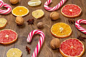 Sweet Christmas cane-lollipops with pieces of dried citrus and nuts