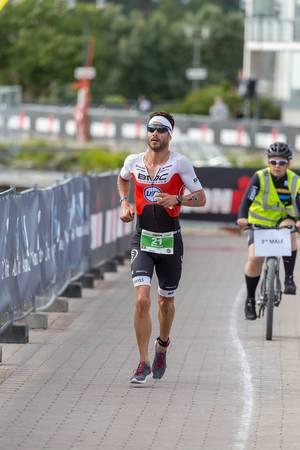 Swiss professional runner Manuel Kueng, shortly before winning a bronze medal, runs the Ironman 70.3 marathon in Lahti, Finland