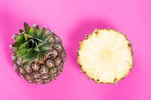 Symmetrisch angeordnete halbierte Ananas auf pinken Hintergrund