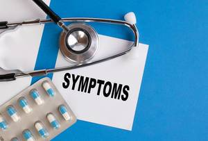 Symptoms written on medical blue folder