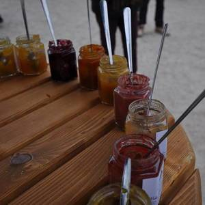 Table of Jars with Different Jams on a Wooden Table at a Market