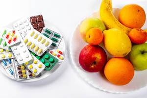 Tablets and fresh fruit on white background. The concept of choosing between a healthy diet and treatment (Flip 2019)