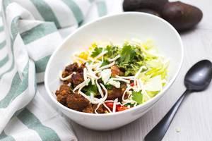 Taco Bowl mit Fleischbällchen, geriebenem Käse und Salat in weißer Schüssel