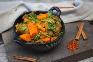 Tajine mit Rindfleisch, Karotten, Zwiebeln und Petersilie mit bereitgelegten Zimtstangen und Safran auf Holzbrett