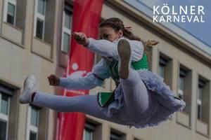 """Tanzmariechen im Kostüm, macht einen Spagatsprung in der Luft, neben dem Bildtitel """"Kölner Karneval"""""""