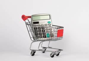 Taschenrechner in Einkaufswagen vor weißem Hintergrund