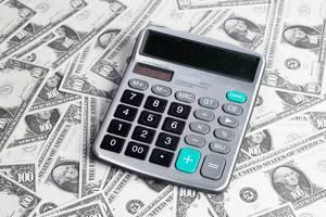 Taschenrechner liegt auf Dollarnoten und steht für Geld sparen, Budget und Preiskalkulation