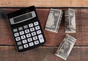 Taschenrechner mit amerikanischem Geld auf einem Holztisch