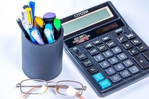 Taschenrechner mit verschiedenen Schreibern in Behälter und Brille vor weißem Hintergrund
