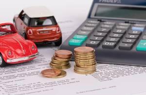 Taschenrechner und Geld mit zwei roten Spielzeugautos und Unterlagen auf Englisch