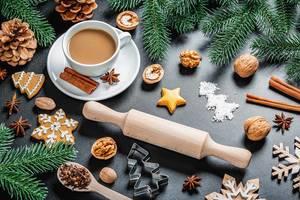 Tasse Kaffee in Weihnachtlicher Dekoration - Backformen und Zutaten, Tannenzweige, Walnüsse, Plätzchen