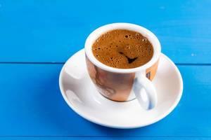 Tasse Kaffee mit Untertasse auf einem blauen Holztisch