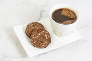 Tasse mit schwarzem Kaffee, neben zwei Schokoladen-Erdnusskeksen