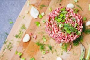 Tatarbeefsteak aus Rinderfleisch, mit grünen Kräutern, Knoblauch und Lauchzwiebel