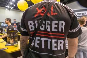 Tätowierter Mann im Bigger-Better T-Shirt steht vor dem Joybräu-Stand auf der Fibo-Messe Köln