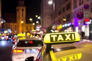 Taxis fahren bei Nacht durch Stadt – im Fokus Taxischild auf Autodach, Stadt mit Bokeh