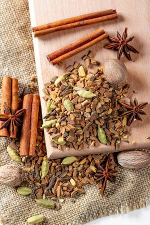 Tea with nutmeg, cloves, cinnamon sticks, star anise on a wooden Board